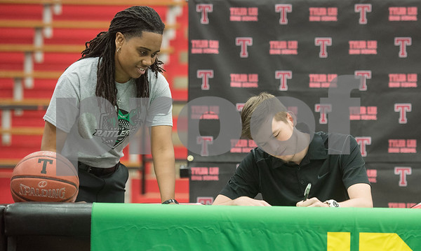 Southwest Collegiate Institute for the Deaf athletic director Roderica Johnson watches Robert E. Lee High School graduate Korbin Casey sign his letter of intent to play collegiate basketball on Wednesday May 16, 2018. Casey will play at Southwest Collegiate Institute for the Deaf. Casey played basketball at REL with assistance from a sign language interpreter.   (Sarah A. Miller/Tyler Morning Telegraph)