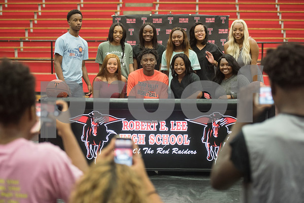 Robert E. Lee High School student Curtis Jones is surrounded by friends after signing his letter of intent to play collegiate basketball at Cedar Valley College on Wednesday May 16, 2018.   (Sarah A. Miller/Tyler Morning Telegraph)