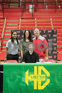 Robert E. Lee High School graduate Korbin Casey takes a photograph with Southwest Collegiate Institute for the Deaf athletic director Roderica Johnson, his mother Kristi Casey and father Kyle Casey after signing his letter of intent to play collegiate basketball on Wednesday May 16, 2018. Casey will play at Southwest Collegiate Institute for the Deaf. Casey played basketball at REL with assistance from a sign language interpreter.   (Sarah A. Miller/Tyler Morning Telegraph)