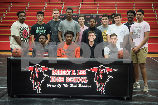 Robert E. Lee High School student Curtis Jones and 2017 graduate Korbin Casey, at center, sign his letters of intent to play collegiate basketball on Wednesday May 16, 2018. Jones will play at Cedar Valley College and Casey will play at Southwest Collegiate Institute for the Deaf.   (Sarah A. Miller/Tyler Morning Telegraph)