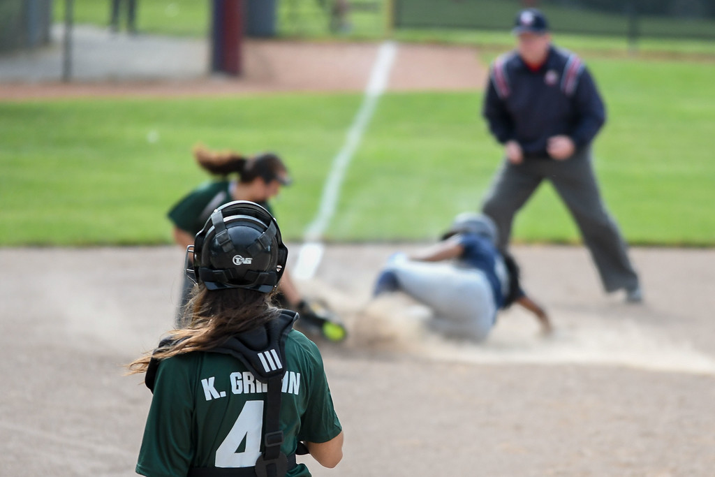. Elyria Catholic catcher Kaylie Griffin watches as her throw to third baseman Olivia Madera is not in time. Eric Bonzar � The Morning Journal