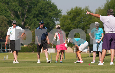 Tonya England crouches low as she watches her ball inch toward the the 12th hole during the Paradise Golf Tournament held Saturday at Emerald Bay Club in Bullard.   (photo by Sarah A. Miller/Tyler Morning Telegraph)