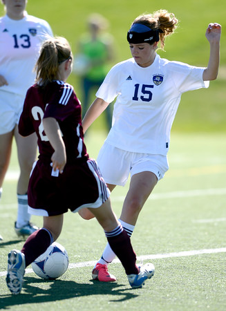 Holy Family's Maddie Kuzik (right) kicks the ball past Berthoud's Hannah Haggas (left) during their soccer game in Broomfield, Colorado May 8, 2012. BOULDER DAILY CAMERA/MARK LEFFINGWELL