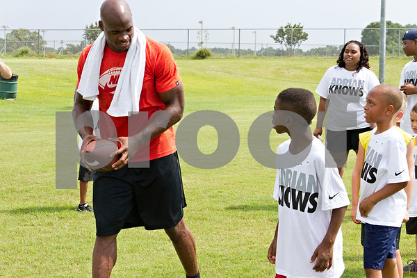 Photo by Shannon Wilson / Tyler Morning Telegraph Adrian Peterson, Minnesota Vikings running back and graduate of Palestine High School in 2004, works with kids on different drills during the Adrian Peterson football camp held at Lindsey Park on Saturday.