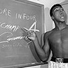 FILE - In this Nov. 15, 1962, file photo, young heavyweight boxer Cassius Clay, who later changed his name to Muhammad Ali,  points to a sign he wrote on a chalk board in his dressing room before his fight against Archie Moore in Los Angeles, predicting he'd knock Moore out in the fourth round, which he went on to do.  The sign also predicts Clay will be the next champ via a knockout over Sonny Liston in eight rounds. He did it in seven rounds. Ali turns 70 on Jan. 17, 2012. (AP Photo/Harold P. Matosian, File)