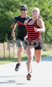 Bonnie Talancon and her father David Talancon, both of Tyler, sprint to the finish line during the Weekend Warrior Race 5K Obstacle Run Saturday morning. The event was held at Camp Tyler and featured 16 obstacles.  (photo by Sarah A. Miller/Tyler Morning Telegraph)