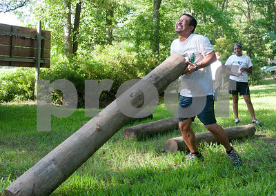 Alex Park of Tyler flips a log, one of 16 obstacles, in the Weekend Warrior Race 5K Obstacle Run. The event was held at Camp Tyler.  (photo by Sarah A. Miller/Tyler Morning Telegraph)