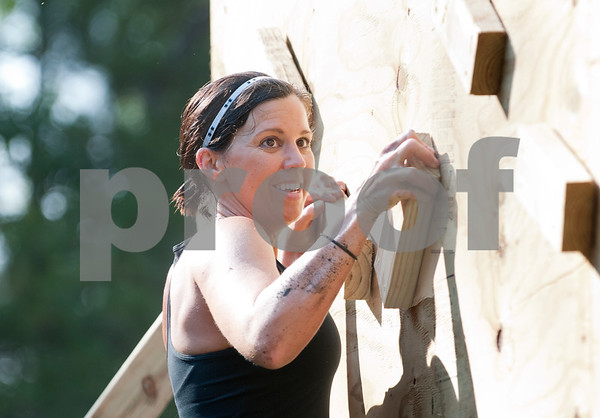 Sarah Johnson of Oklahoma climbs across a wooden wall, one of 16 obstacles, in the Weekend Warrior Race 5K Obstacle Run. The event was held at Camp Tyler.  (photo by Sarah A. Miller/Tyler Morning Telegraph)