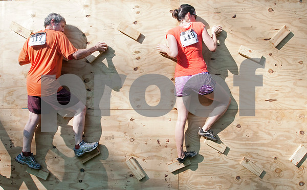 Participants in the Weekend Warrior Race 5K Obstacle Run climb across a wooden wall Saturday morning. The event was held at Camp Tyler.  (photo by Sarah A. Miller/Tyler Morning Telegraph)