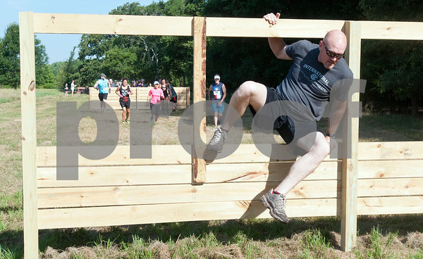 A participants in the Weekend Warrior Race 5K Obstacle Run jumps through a wooden structure Saturday morning. The event was held at Camp Tyler and featured 16 obstacles.  (photo by Sarah A. Miller/Tyler Morning Telegraph)