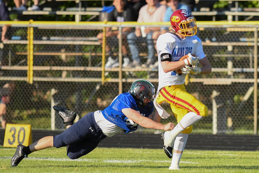 . Avon Lake\'s Mike Davis (11) is brought down by North Ridgeville\'s Ian McDonald (33) after a big gain. Eric Bonzar � The Morning Journal