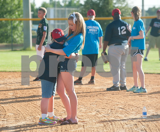 Rose Capital Tyler East Challenger Division player Victoria Bullock hugs her helper during their game against Santa Fe in the 46th annual Texas East State Little League Tournament Saturday July 18, 2015 at Faulkner Park in Tyler, Texas. This is the13th year Tyler has hosted the event. Challenger Division teams have both male and female players from ages 4 through high school students who have mental or physical special needs.  (photo by Sarah A. Miller/Tyler Morning Telegraph)
