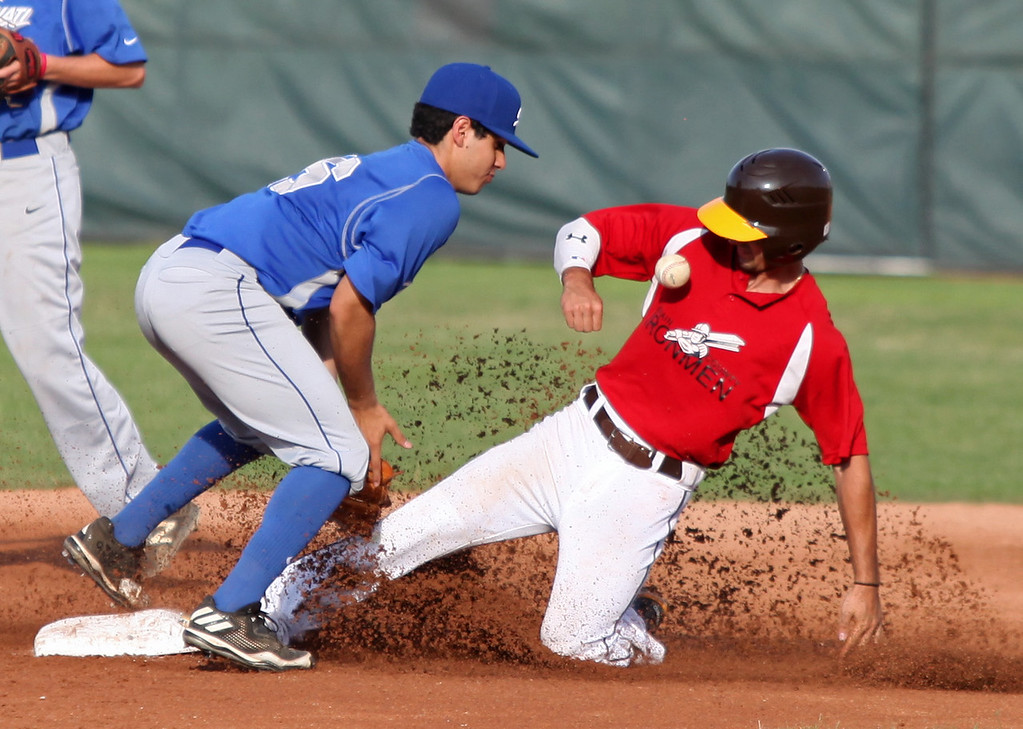 . Chase Knodle of the Ironmen slides into second safely as Aldo Buendia of Cincinnati loses the ball. Randy Meyers -- The Morning Journal