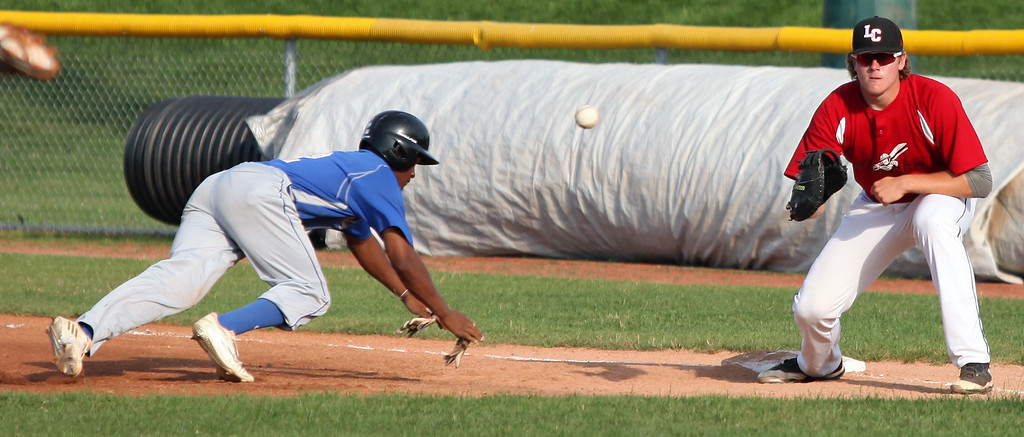 . Cincinnati\'s Jace Mercer dives back to first as the throw comes in to Ironmen first baseman Jaret Peterson. Randy Meyers -- The Morning Journal