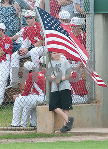 photo by Sarah A. Miller/Tyler Morning Telegraph  Collin Boyd, 10, of Tyler, holds an American flag as he waits to take the field for the National Anthem during the opening ceremonies of the 44th Annual Texas East League State Tournament Saturday at Faulkner Park in Tyler. This is the 11th year the tournament has been held in Tyler.