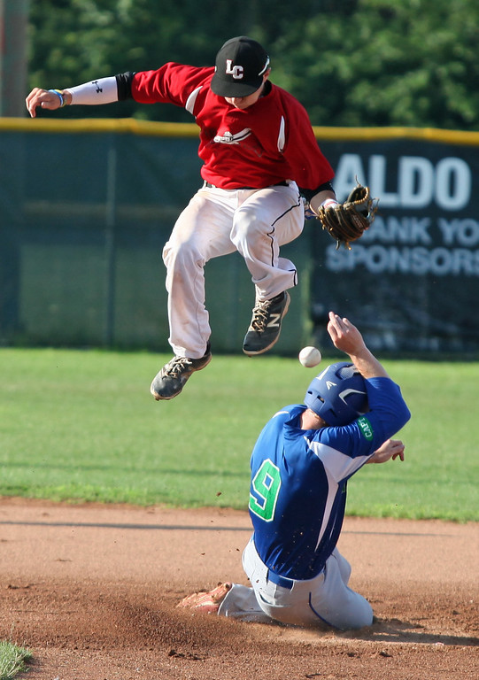 . Randy Meyers - The Morning Journal<br> Ironmen infielder Nicholas Novak leaps over Joe Aeilts of Grand Lake at second base and loses the ball on July 22 at The Pipe Yard.