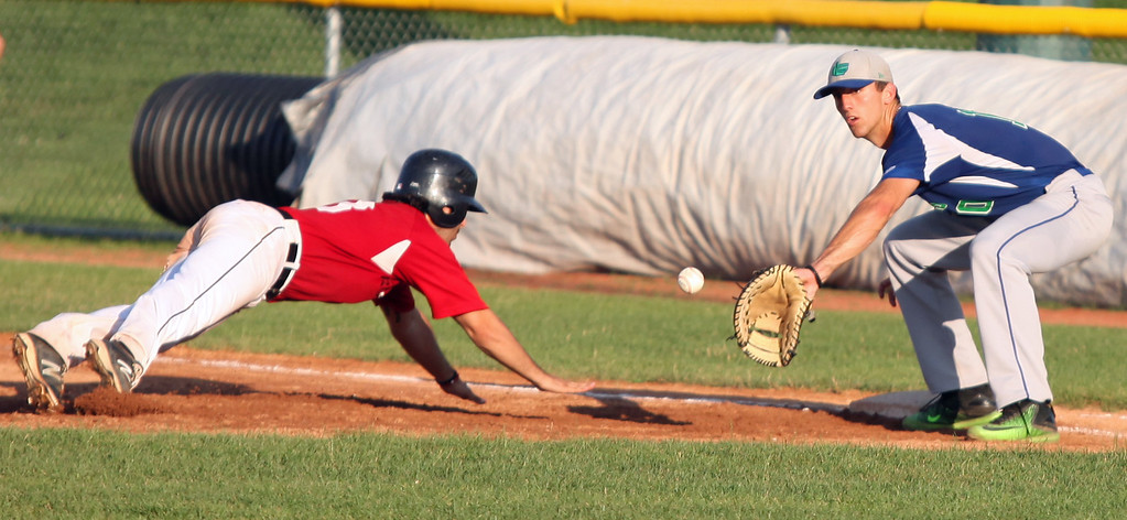 . Randy Meyers - The Morning Journal<br> Sam Casinelli of the Ironmen dives back to first safely before the ball is caught by Grand Lake\'s Tucker Linder on July 22.