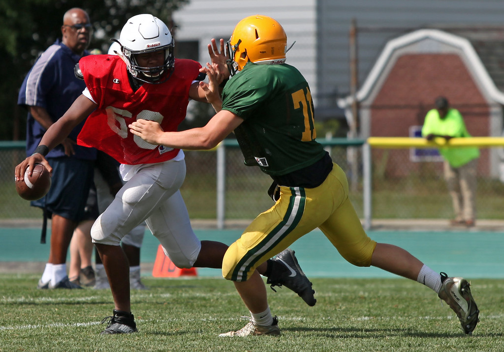 . Lorain quarterback Jordan Jackson is pressured by the Amherst defense during a scrimmage. Randy Meyers -- The Morning Journal