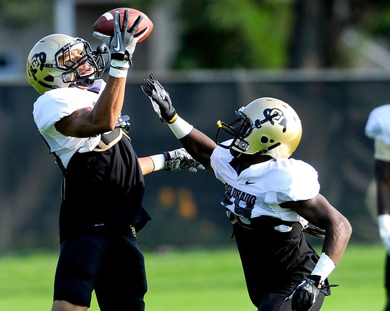 CU defensive back Greg Henderson (left) catches the ball while being defended by defensive back Harrison Hunter (right) during practice at the University of Colorado in Boulder, Colorado August 14, 2012.  DAILY CAMERA MARK LEFFINGWELL