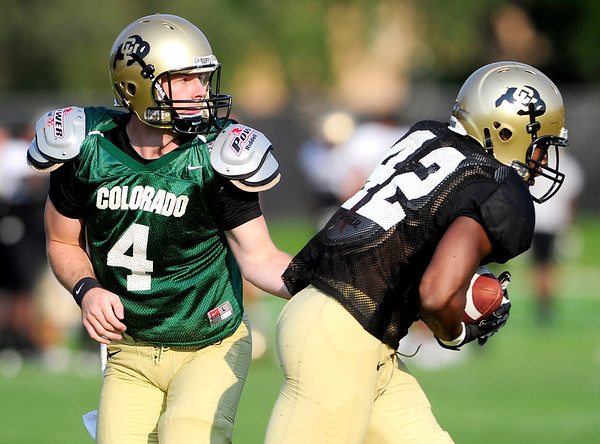 CU quarterback Jordan Webb (left) hands the ball off to tailback Josh Ford during practice at the University of Colorado in Boulder, Colorado August 14, 2012.  DAILY CAMERA MARK LEFFINGWELL