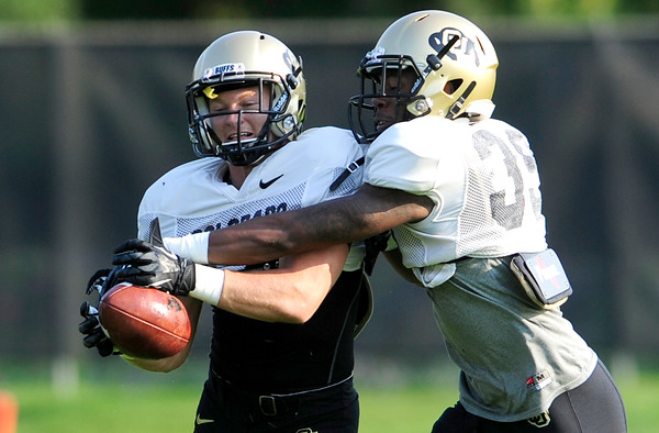 CU cornerback Josh Moten (right) knocks the ball from the hands of  defensive back Josh Orms (left) during practice at the University of Colorado in Boulder, Colorado August 14, 2012.  DAILY CAMERA MARK LEFFINGWELL