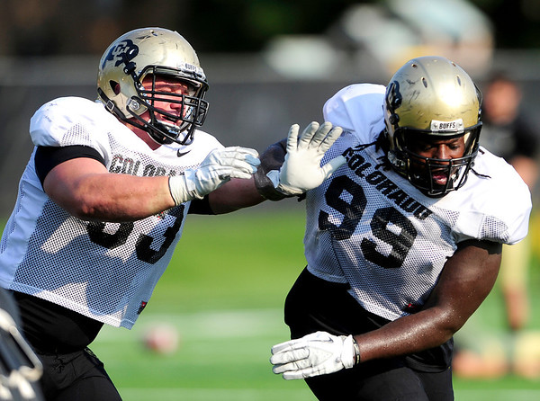 CU defensive tackle Will Pericak (left) shoves defensive lineman Nate Bonsu (right) during practice at the University of Colorado in Boulder, Colorado August 14, 2012.  DAILY CAMERA MARK LEFFINGWELL