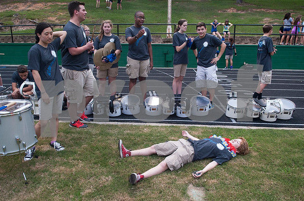 Grace Community School drum line pit member junior Nicole Hensley rests on the ground after running to put rain covers on instruments during the Azalea Orthopedics and Texas Spine & Joint Hospital Tyler Football Classic at McCallum Stadium on the campus of Bishop Thomas K. Gorman Regional Catholic School Friday night August 26, 2016.  (Sarah A. Miller/Tyler Morning Telegraph)
