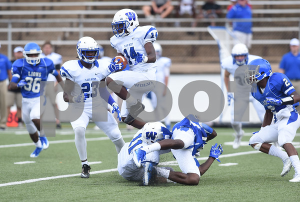 Plano West's Tapatrick Martin jumps over two players as he carries the ball during their game against John Tyler High School Saturday August 27, 2016 at Christus Trinity Mother Frances Rose Stadium.  (Sarah A. Miller/Tyler Morning Telegraph)