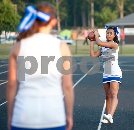 photo by Sarah A. Miller/Tyler Morning Telegraph  Frankston High School cheerleader sophomore Kaitlyn Mills, 15, throws a football to junior Morgan Hart, 16, as they wait for the game to begin Thursday night at Brook Hill.