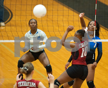 photo by Sarah A. Miller/Tyler Morning Telegraph  Texarkana Arkansas High School's (10) Alexus Paxton looks back after John Tyler's (7) Chenique Baxter spikes the ball to their side Friday afternoon during the Tyler Volleyball Tournament at John Tyler High School.