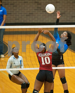 photo by Sarah A. Miller/Tyler Morning Telegraph  John Tyler's (7) Chenique Baxter spikes the ball as Texarkana Arkansas High School's (10) Alexus Paxton tries to block it Friday afternoon during the Tyler Volleyball Tournament at John Tyler High School.