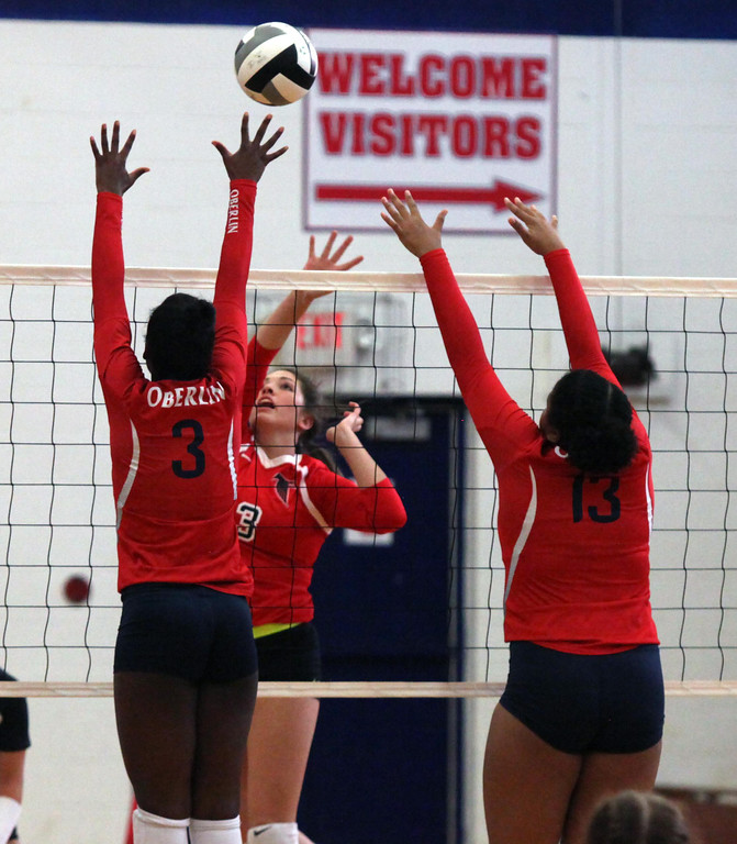 . Bianca Inman of Firelands taps the ball over Nya Grady-Norman of Oberlin at the net. Randy Meyers -- The Morning Journal