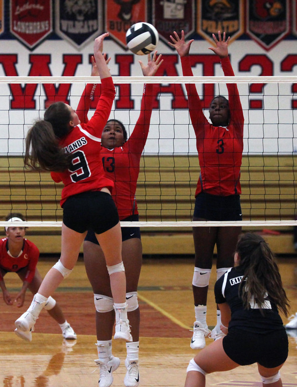 . Firelands Emily Squires spikes the ball over Tiffani Burke and Nya Grady- Norman of Oberlin. Randy Meyers -- The Morning Journal