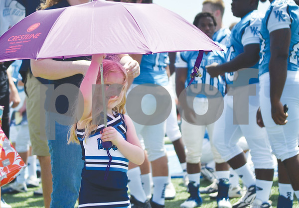 Daughter of defensive line coach David Lacy, Sophia, 4, tries to stay out of the sun on Thursday during West Rusk High School football media day. (Victor Texcucano)