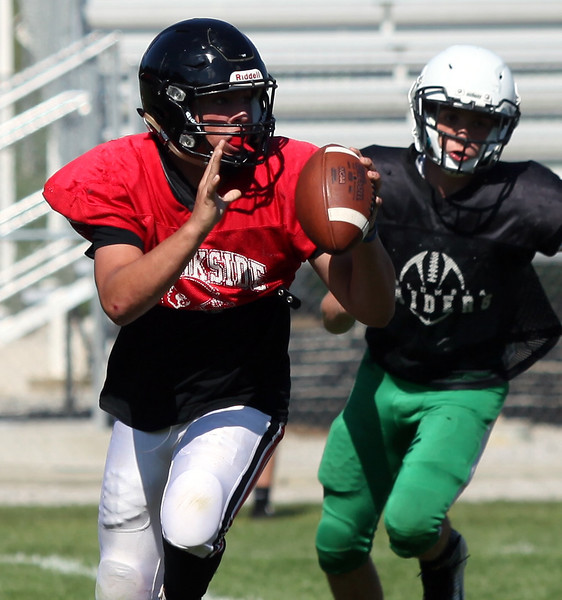 Brookside quarterback Jonathan Hice rolls to his right and away from the Columbia pass rush. Randy Meyers -- The Morning Journal