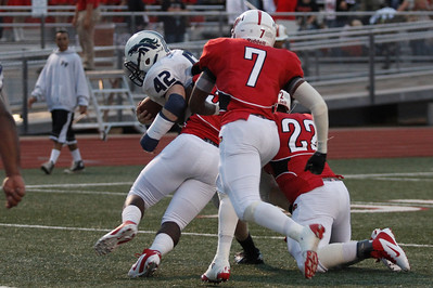 Del Valle players tackle McNeil's Matthew Zebrowski Friday at Veterans Stadium.