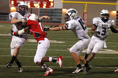 McNeil's Colton Russell is taken down by Del Valle's Kenneth Caldwell Friday at Veterans Stadium.