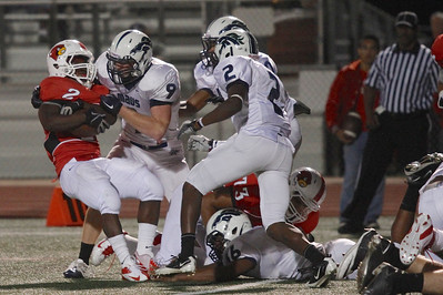 Del Valle's Josh Cleveland is taken down by McNeils Zach Vaughan Friday at Veterans Stadium.