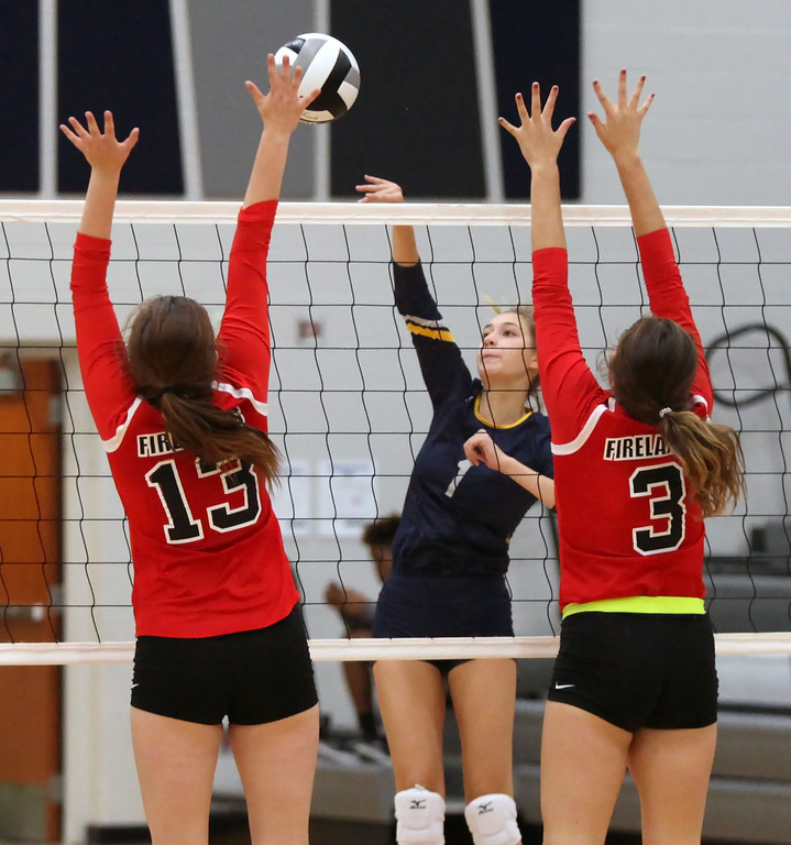 . Maia Wasuk of North Ridgeville spikes the ball at Taylor Kenska and Bianca Inman of Firelands during the first set. Randy Meyers -- The Morning Journal