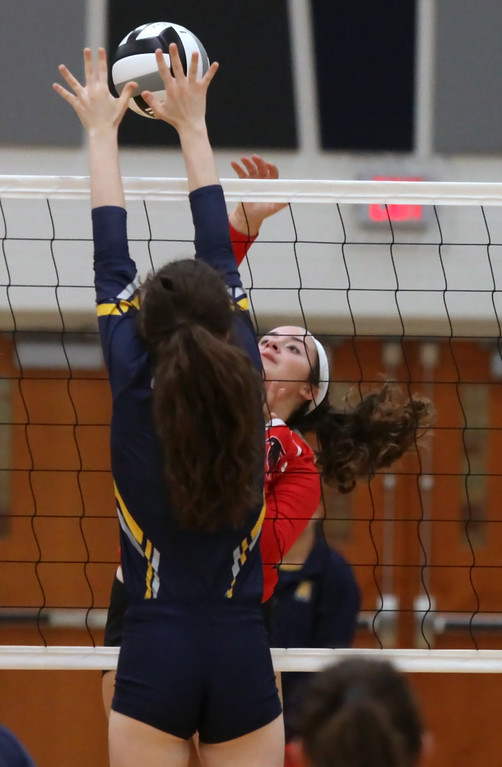 . Jamison Turay of North Ridgeville partially blocks the spike by Samantha Walcott of Firelands during the first set. Randy Meyers -- The Morning Journal