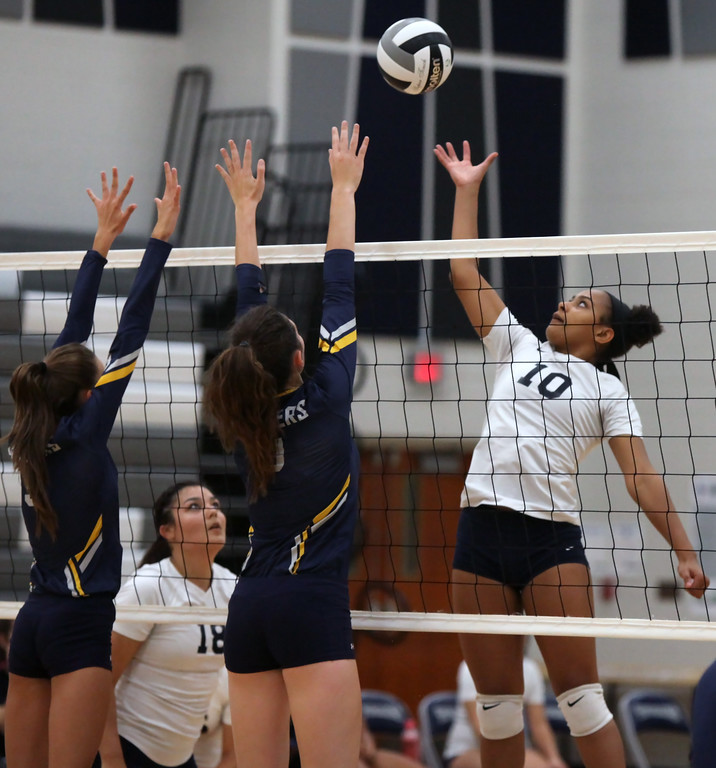 . Lorain\'s Sydney Patterson taps the ball over Jamison Turay, left, and Callista Wasuk of North Ridgeville. Randy Meyers -- The Morning Journal