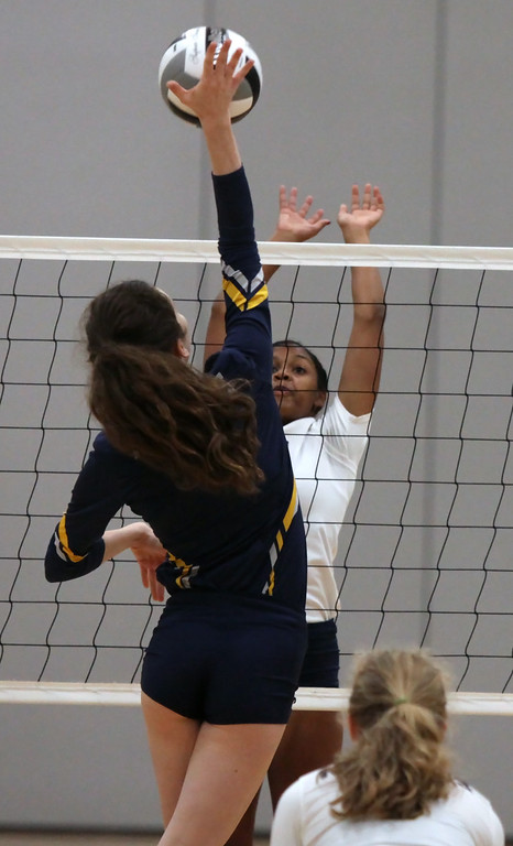 . Molly Flanagan of North Ridgeville spikes the ball over Sydney Patterson of Lorain during the first set. Randy Meyers -- The Morning Journal