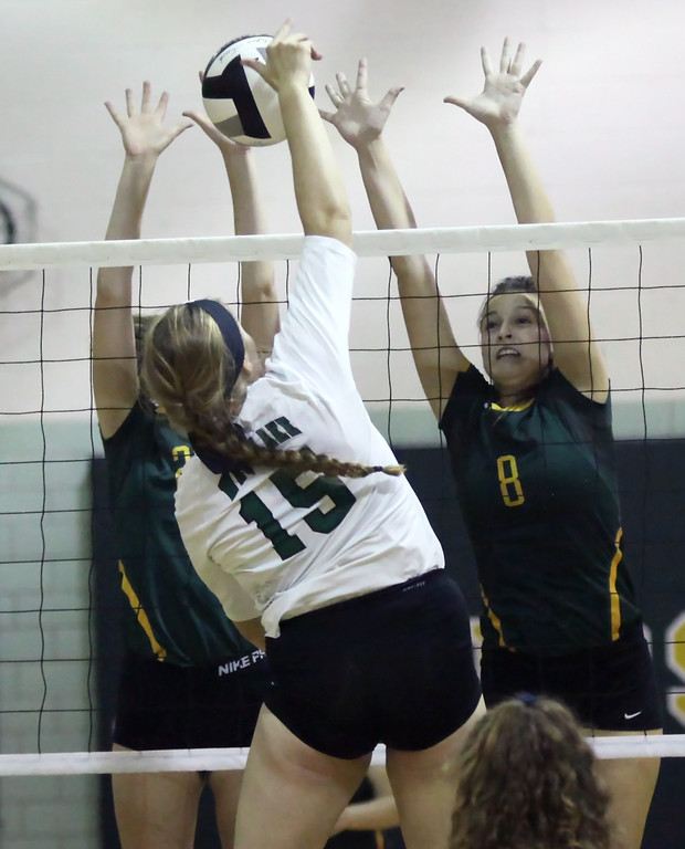 . Sarah Farley and Sarah Weigand of Amherst block the spike attempt by Audrey Lyle of Westlake during the second set. Randy Meyers -- The Morning Journal