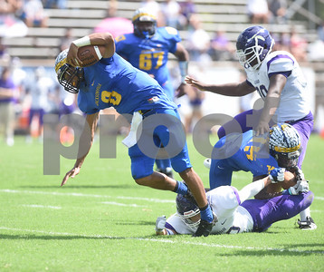 Jacksonville High School's Cameron High is tripped up by Alvarado's Jacob Shockley at the Tomato Bowl Saturday Sept. 24, 2016.  (Sarah A. Miller/Tyler Morning Telegraph)