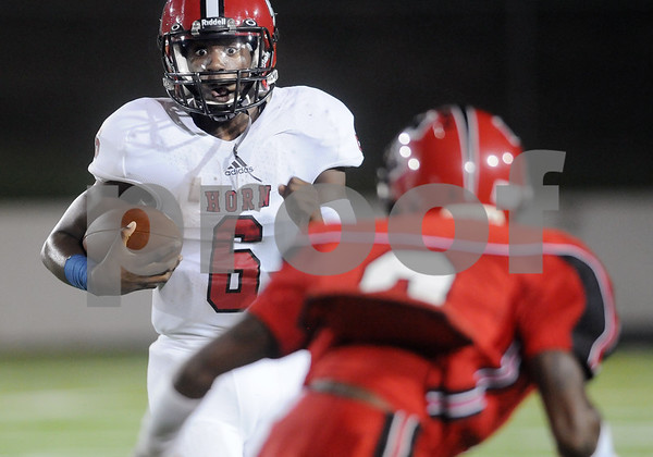 photo by Sarah A. Miller/Tyler Morning Telegraph  Mesquite Horn's quarterback junior Destri White looks for a way past Robert E. Lee's senior Davier Harris Friday night at Trinity Mother Frances Rose Stadium in Tyler.