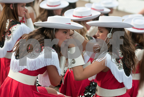 photo by Sarah A. Miller/Tyler Morning Telegraph   Robert E. Lee Southern Belle drill team members put on their hats before the start of the football game between Robert E. Lee High School and Lufkin Friday night at Trinity Mother Frances Rose Stadium in Tyler.