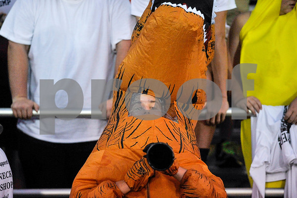 A White Oak fan blows a horn in a T-Rex costume during a high school football game at Bishop T.K. Gorman Catholic High School in Tyler, Texas, on Friday, Sept. 8, 2017. (Chelsea Purgahn/Tyler Morning Telegraph)