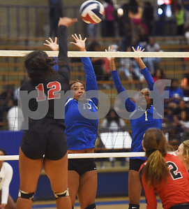 Robert E. Lee's De'Ja Hamilton spikes the ball toward John Tyler's Avoree Oliver and Andreanna Ellison during their volleyball game at the Lions Den Friday night Sept. 9, 2016.  (Sarah A. Miller/Tyler Morning Telegraph)