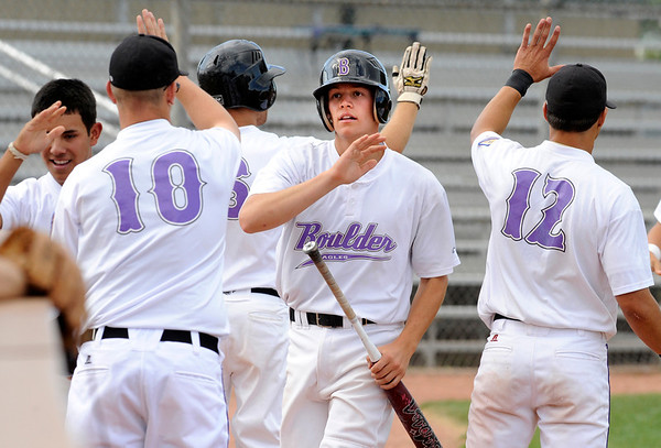 Phillipe Guegan #2, is congratulated by Boulder Eagles teammates including Chase Vermillion, #10 and John Anagnost, #12 as Guegan scored one of 3 runs of a RBI double in the first inning during their Legion A baseball against the Boulder Wells Fargo Advisors at Scott Carpenter Park on Monday. Guegan knocked in the teams first run of the game on a RBI single.<br /> Photo by Paul Aiken / The Camera / July 25, 2011