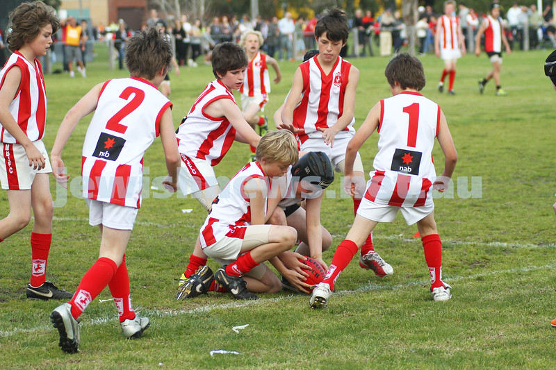 28-8-11. AJAX Under 12 Jets premiers 2011, defeating Mordialloc Braeside. Ryan Marks holds off 6 opposition players. Photo: Peter Haskin